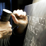 A man carving letters into stone
